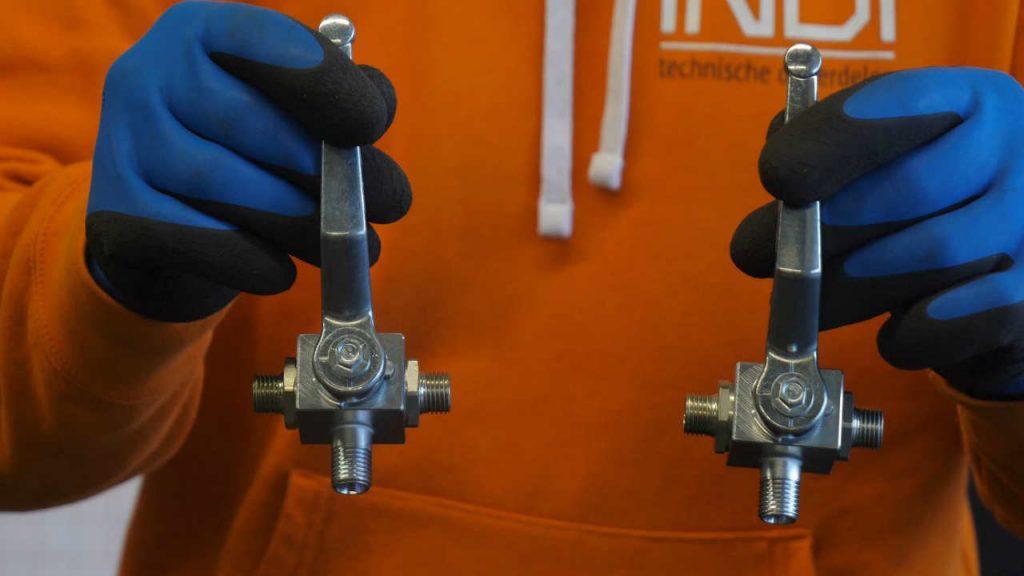 Productspecialist Eerjan houdt een driewegkraan met een L-boring en een driewegkraan met een T-boring vast