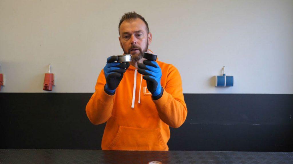 Eerjan houdt een manometer kunststof van kunststof en een manometer van RVS vast