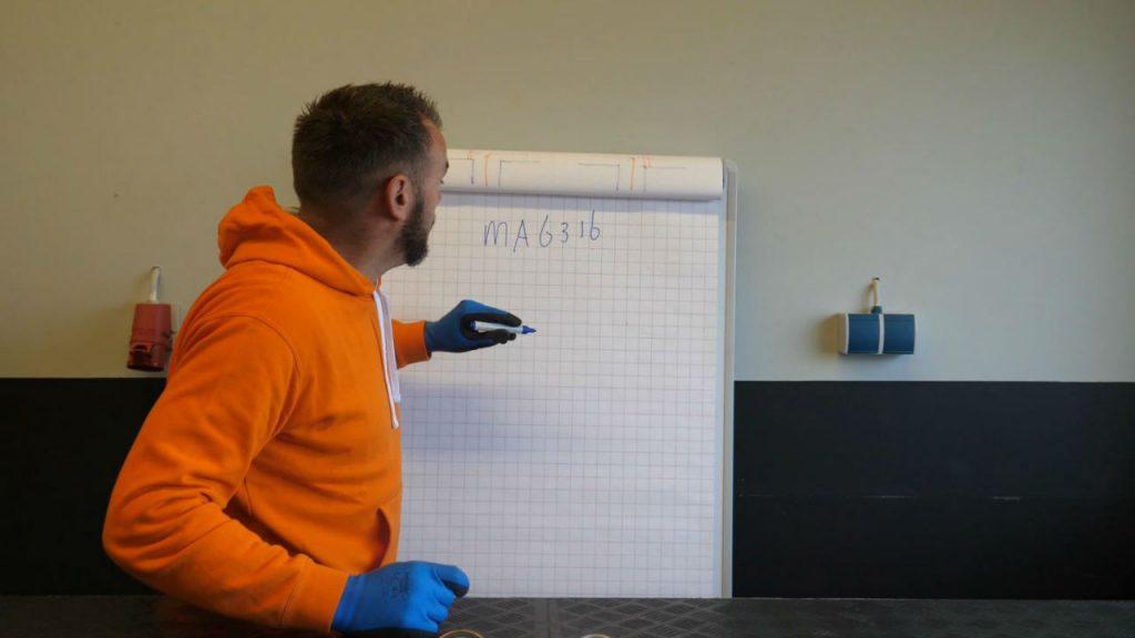 Eerjan toont bij het whiteboard de codering van manometers