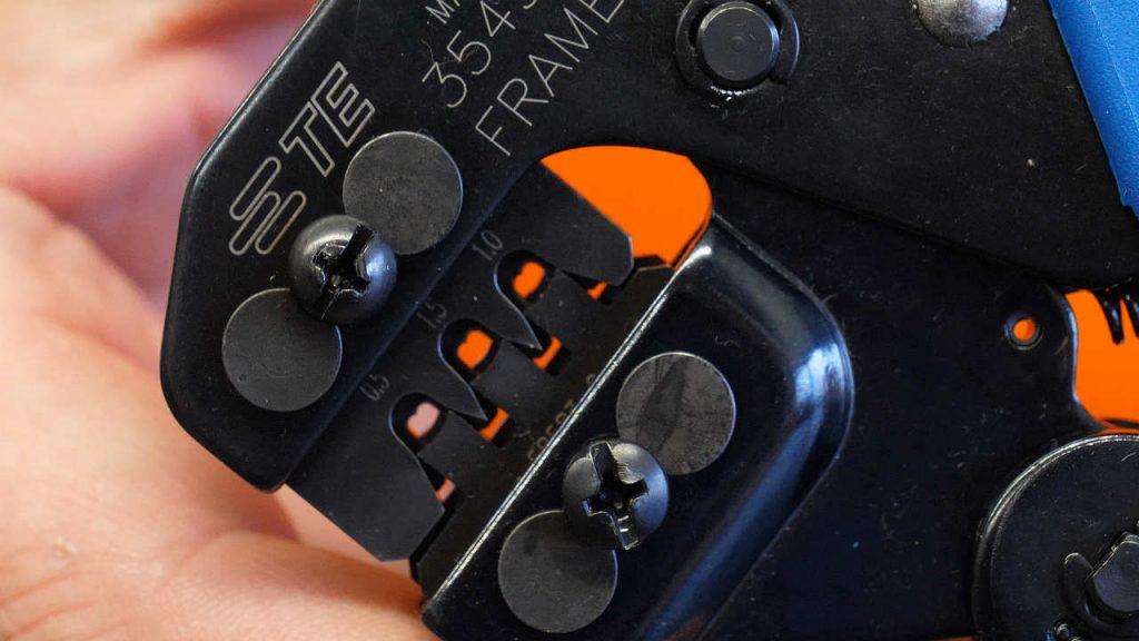 close-up van de tang voor et plaatsen van de rubbers aan de klemmen.