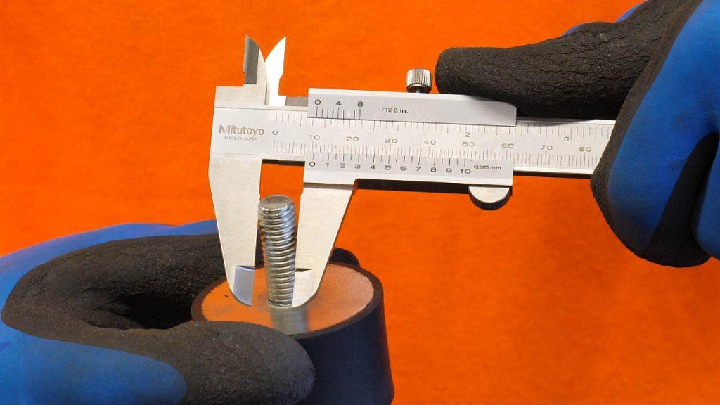 een schuifmaat gebruiken om een trillingsdemper te meten (schroefdraad).