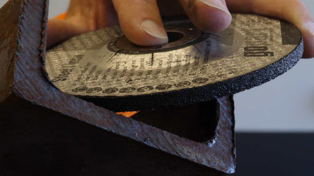 Close-up van een afbraamschijf op een U-profiel waarop de bramen aan de rand zichtbaar zijn