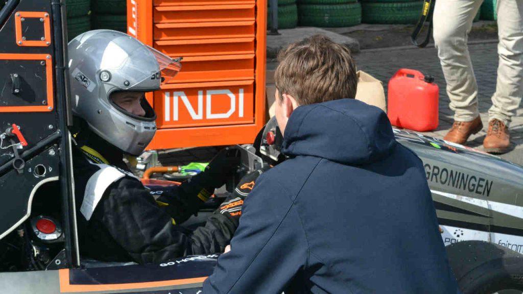 De coureur van de nummer 4 raceauto overlegt