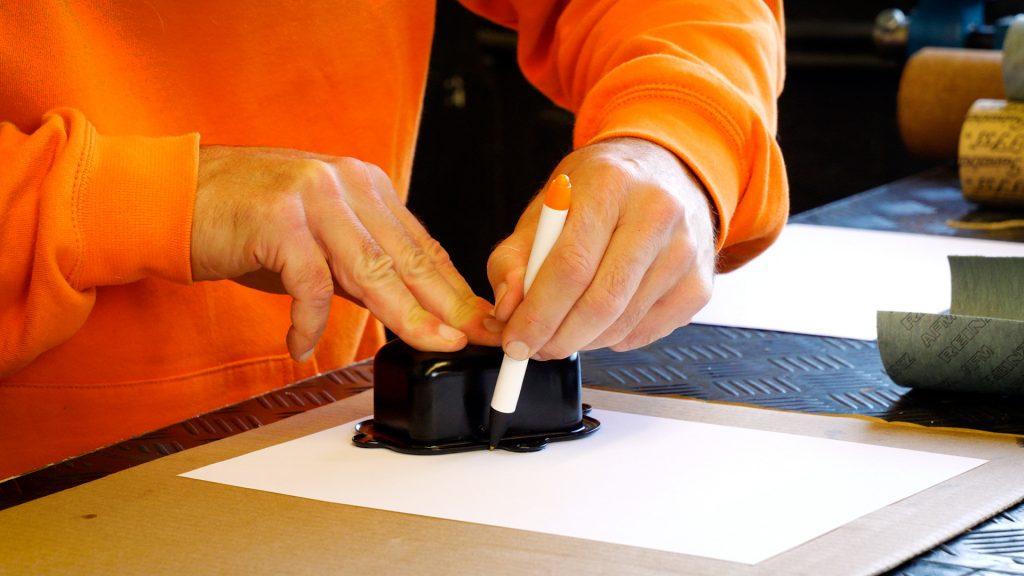 Eerjan trekt met een pen de omtrek van het deksel op het papier en karton