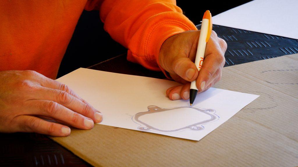 Eerjan trekt de lijnen van de olieafdruk na met een pen op het papier